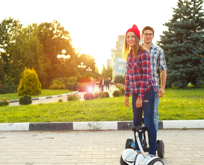 Young couple riding hoverboard - electrical scooter, personal ec stock photo