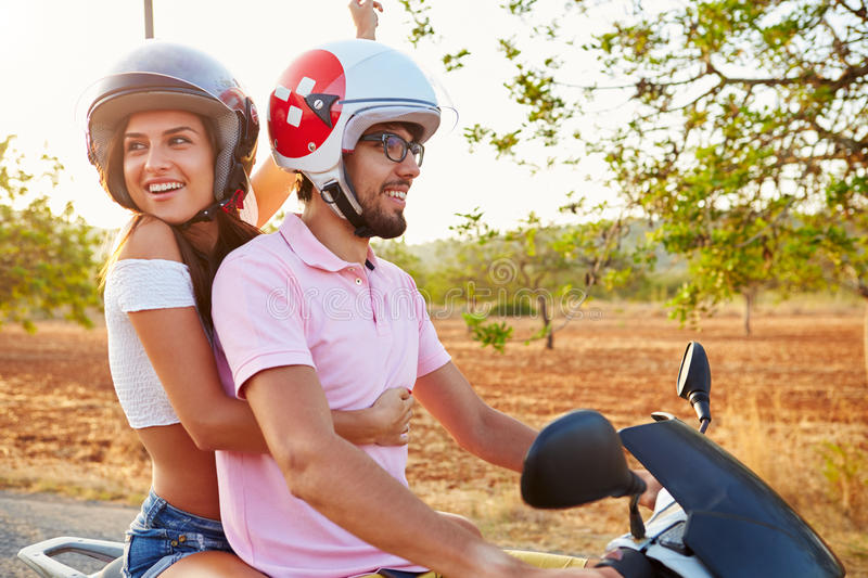 Young Couple Riding Motor Scooter Along Country Road royalty free stock photos