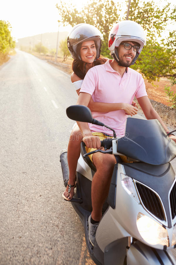 Young Couple Riding Motor Scooter Along Country Road royalty free stock images