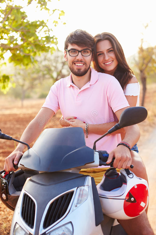 Young Couple Riding Motor Scooter Along Country Road stock image