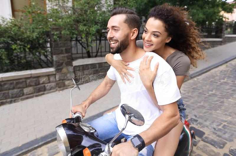 Young couple riding motor scooter in city royalty free stock photo