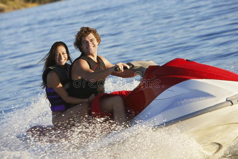 Young Couple Riding PWC stock photography