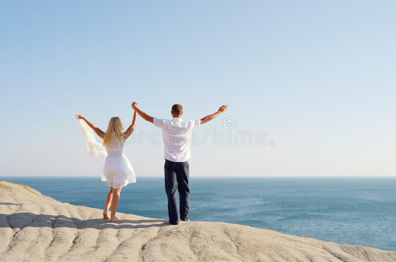 Young couple on a rock raised hands to the sky