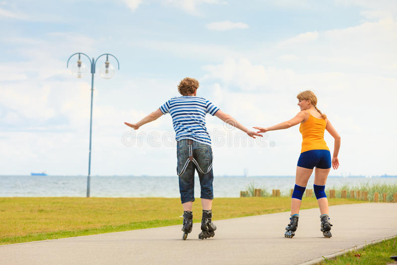 Young couple on roller skates riding outdoors. Holidays, active people and friendship concept. Young fit couple on roller skates riding outdoors on sea shore royalty free stock photo
