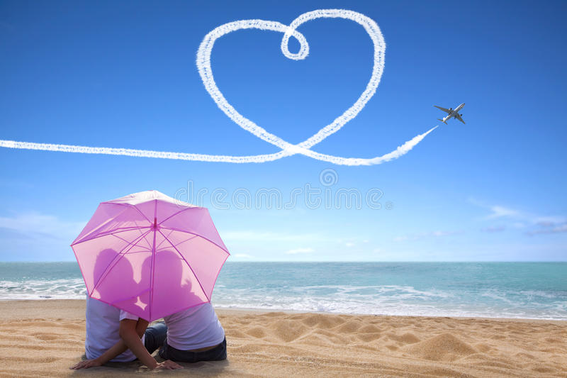 Young couple romantic kissing at the beach with the umbrella royalty free stock images