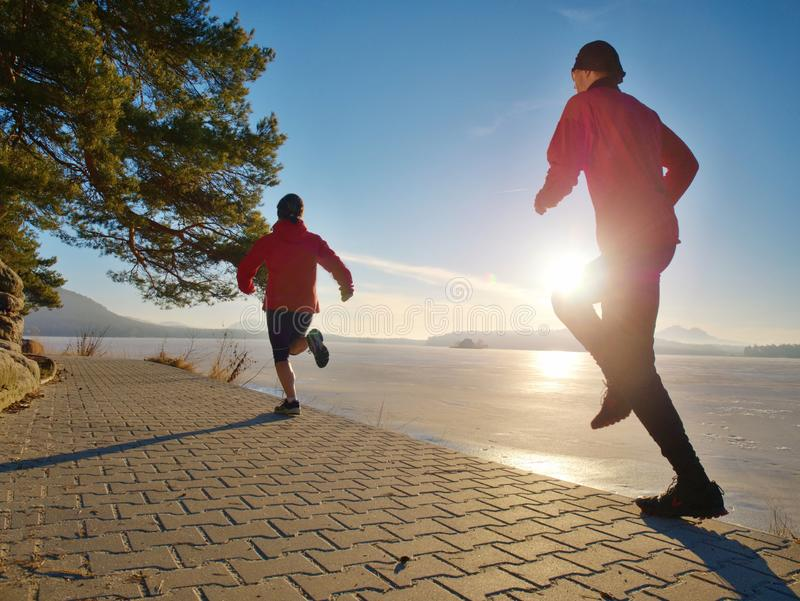 Young couple of runners during regular workout. Young couple of runners during regular outdoor morning workout run at frozen lake working winter wellness weight royalty free stock photos
