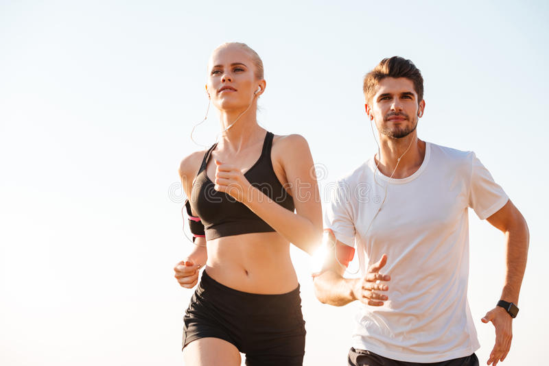 Young couple runners training outdoors. Young couple runners training together outdoors stock images