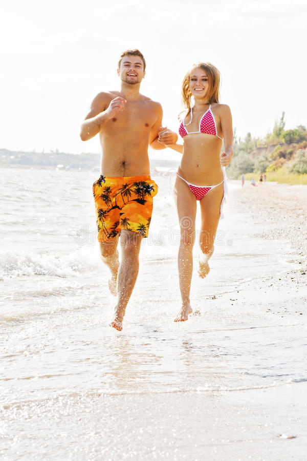 Download Young Couple Running Along The Beach Stock Image - Image of outdoors, copy: 11401989