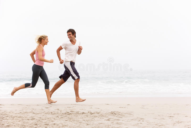 Download Young Couple Running Along Winter Beach Stock Image - Image: 15253631