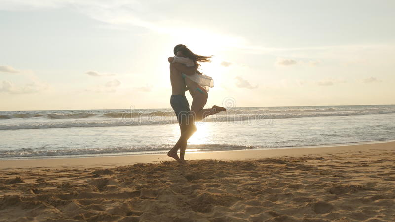 Young couple is running on the beach, man hug and spin around his woman on sunset. Girl jumps into her boyfriend arms royalty free stock photography