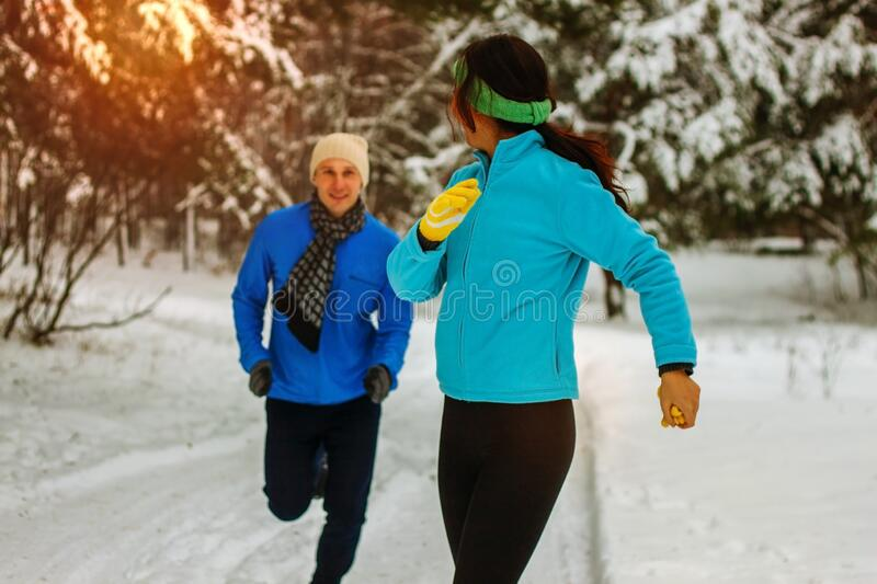 Young couple running dressed warmly in fleeces and gloves jogging in sunshine across winter snow royalty free stock photos