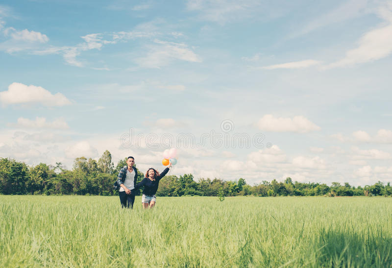 Young Couple running and holding balloon in the green grass below the blue sky look so happy. stock images