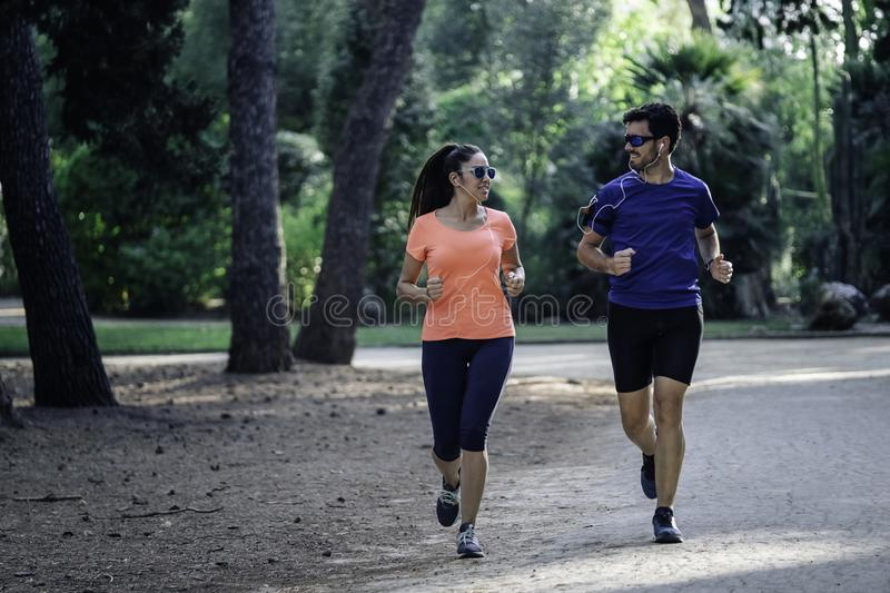 Young couple running through the park and listening to music. healthy living concept stock photography