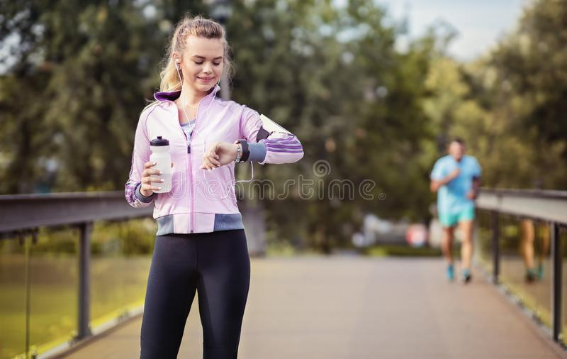 Young couple running in the park at morning. Woman timing her jogging male partner royalty free stock photography