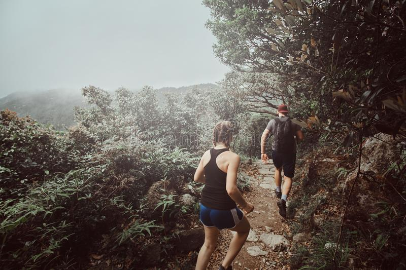 Young couple is running by the path in foresty mountains. There are green thickets and trees around. Fog and clouds at background stock photos