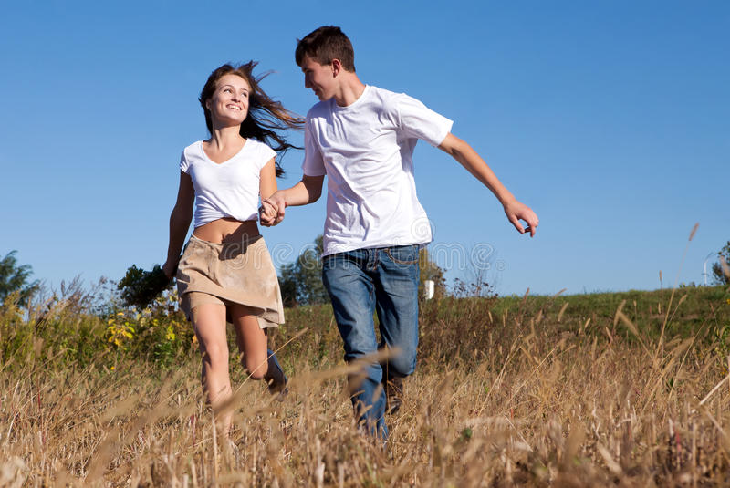 Young Couple Running On Summer Meadow Stock Photo