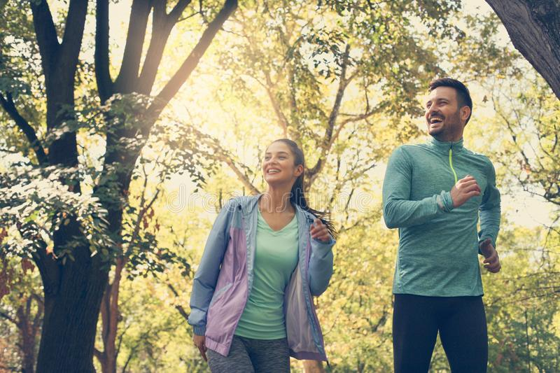 Young couple running together in park. Young people exercising. royalty free stock photography