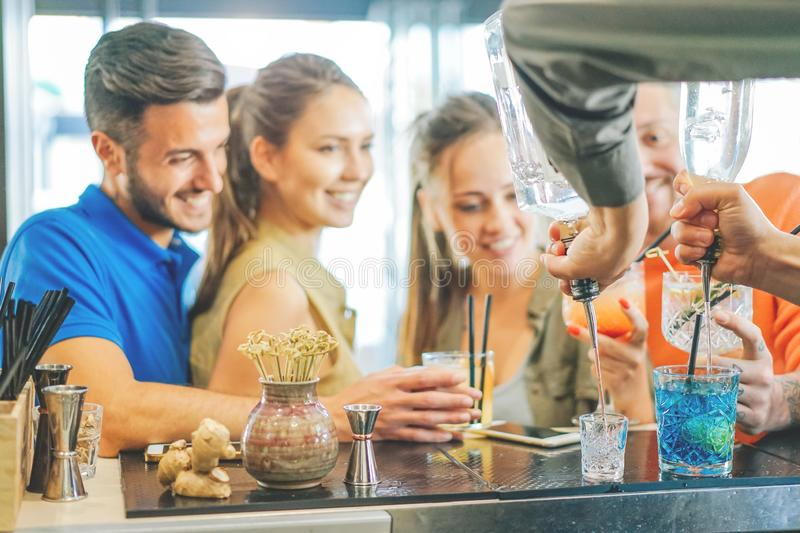 Young couple`s of friends drinking cocktails at the bar counter - Bartender preparing colorful cocktail stock photo