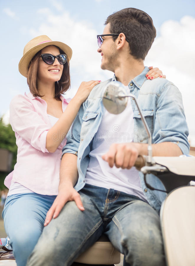 Young couple on scooter. Young romantic couple sitting on scooter together and looking to each other royalty free stock photos
