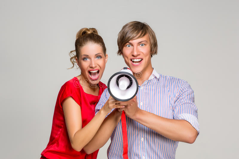 Young couple screaming in bullhorn. Beautiful happy young couple screaming at megaphone. handsome men and girl together. copy space stock photography