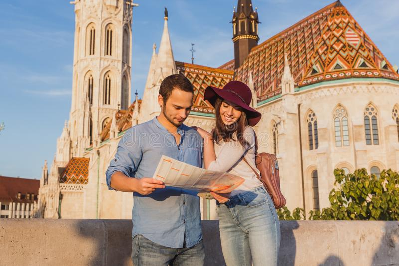 Young couple searching right direction on map from the point from Fisherman Bastion in Budapest with Matthias Church on. Background during sunrise stock image