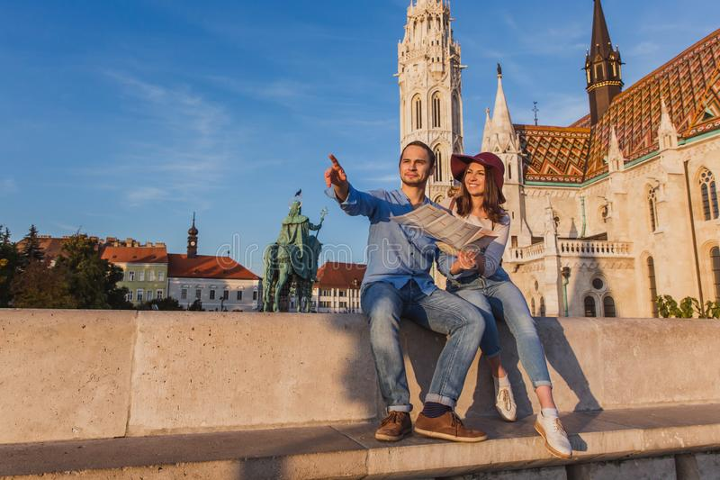 Young couple searching right direction on map from the point from Fisherman Bastion in Budapest with Matthias Church on. Background during sunrise stock photo