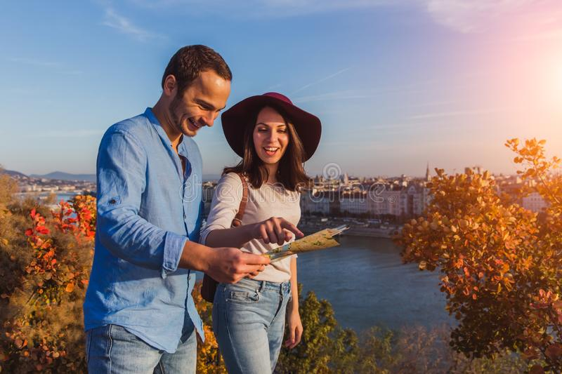 Young couple searching right direction on map from the point from Gellert Hill in Budapest during sunrise. In autumn royalty free stock image