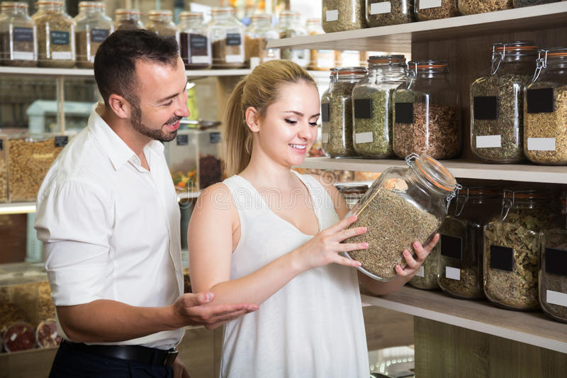 Young couple selecting dried herbs in organic shop. Young couple selecting dried herbs and women holding glass can in organic shop royalty free stock images
