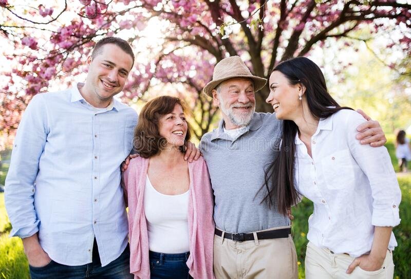 Young couple with senior parents walking outside in spring nature. royalty free stock images