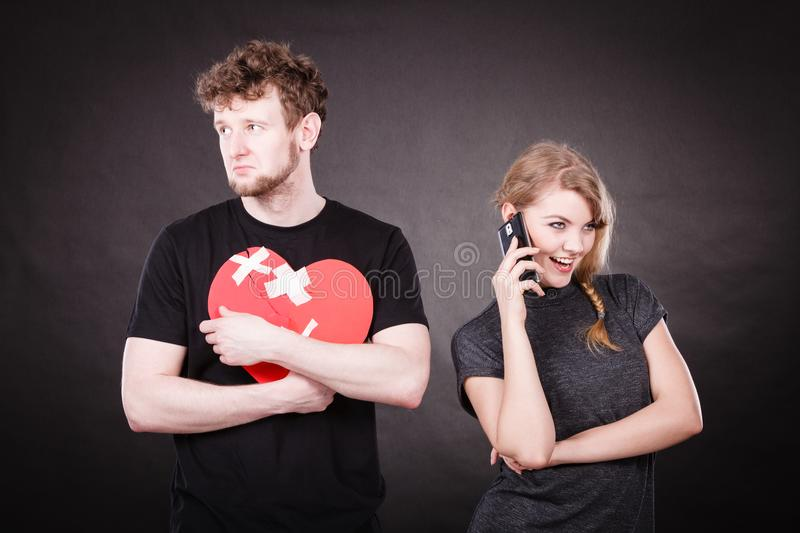Young couple in separation because of betrayal. Betrayal and break up. Young attractive blonde women calling flirting by mobile phone. Sad handsome men with stock photos