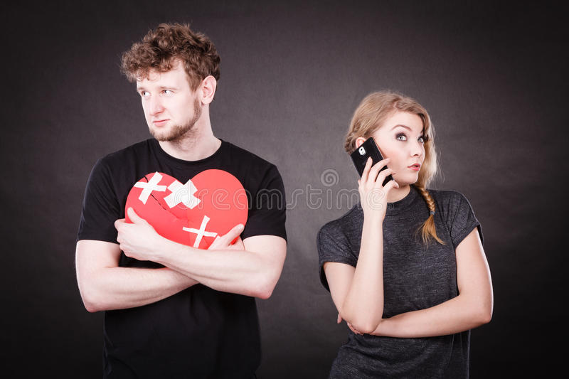 Young couple in separation because of betrayal. Betrayal and break up. Young attractive blonde women calling flirting by mobile phone. Sad handsome men with royalty free stock photos