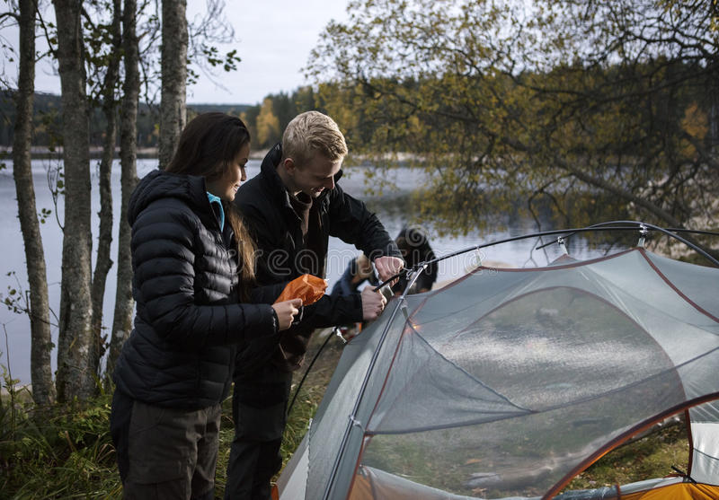 Young Couple Setting Up Tent By Lake royalty free stock photography