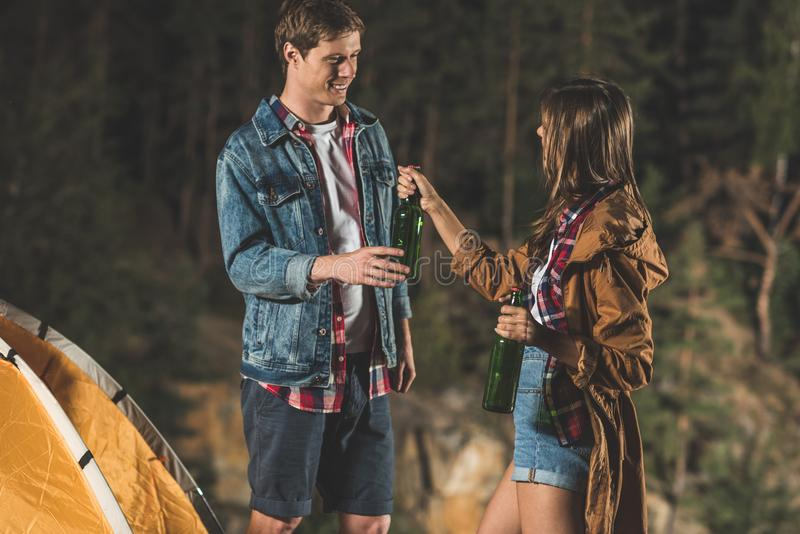 Young couple sharing beer in hiking trip. At night royalty free stock image