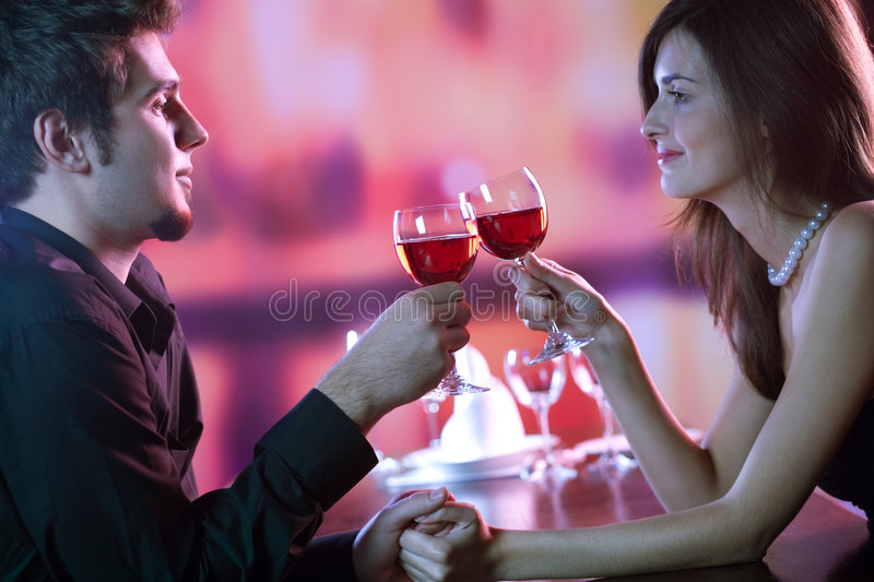 Young couple sharing a glass of red wine in restaurant, celebrating or on romantic date stock image