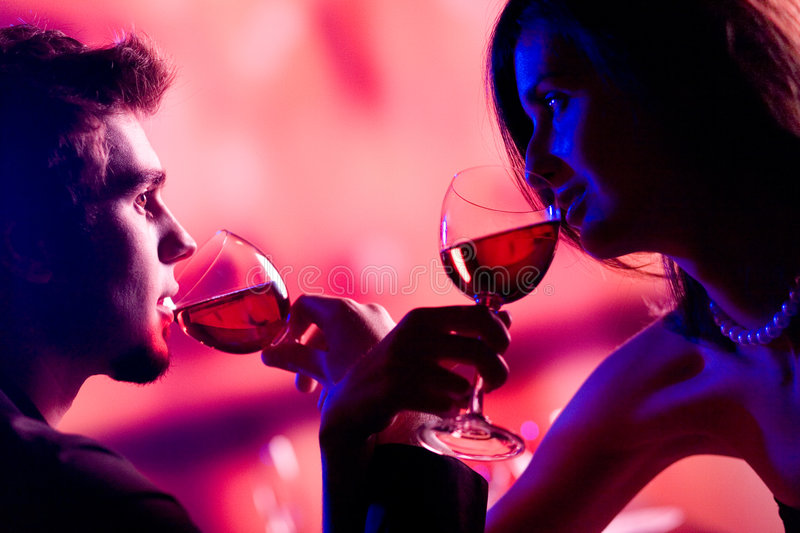 Young couple sharing a glass of red wine in restaurant, celebrating or on romantic date stock photography
