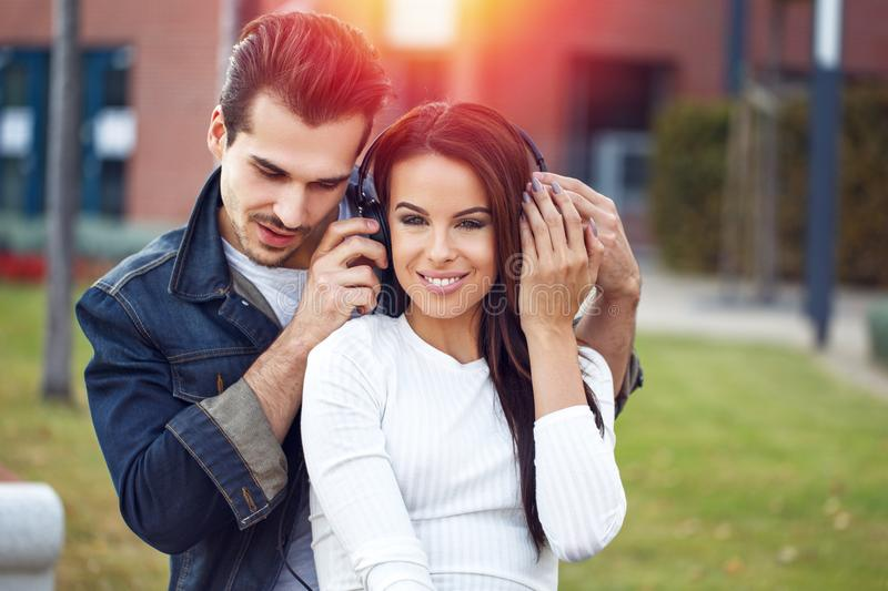 Young couple sharing music by headphones stock image