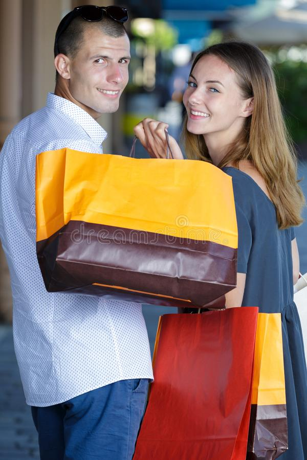 Young couple with shopping bags looking at camera. Couple royalty free stock image