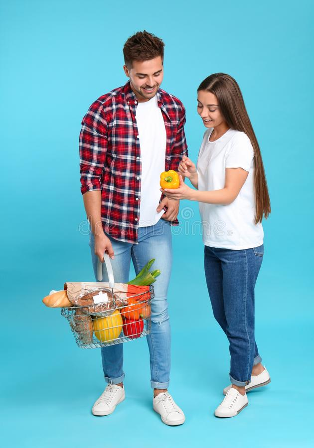 Young couple with shopping  full of products on blue background stock photos