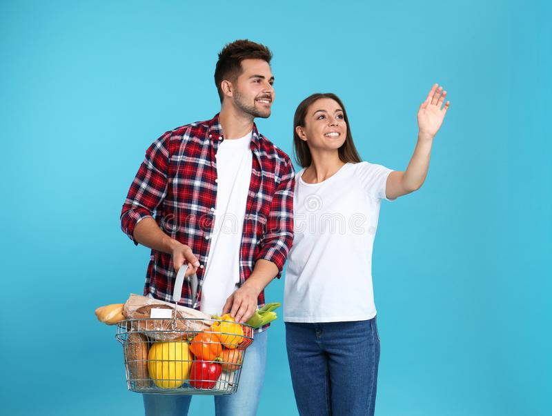 Young couple with  basket full of products on blue background royalty free stock photo