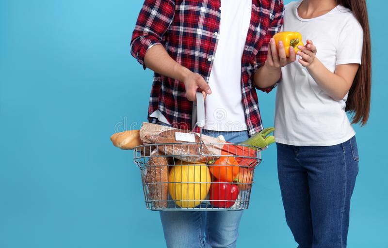 Young couple with shopping  full of products on blue background royalty free stock images