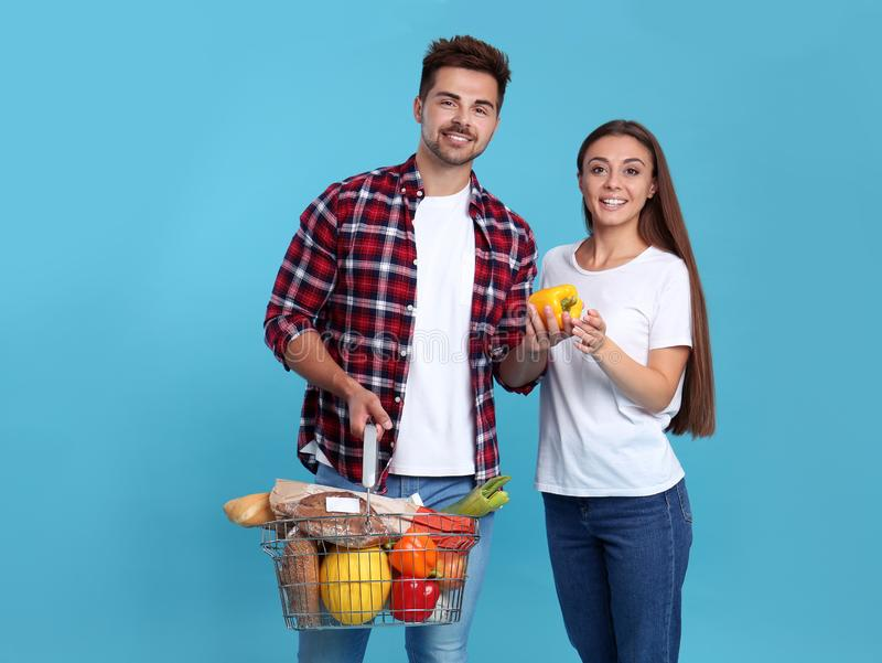 Young couple with shopping basket full of products on background. Young couple with shopping basket full of products on blue background stock photography
