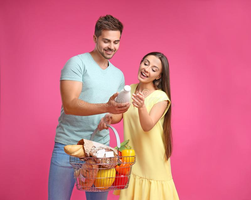 Young couple with shopping  full of products on pink background royalty free stock photos