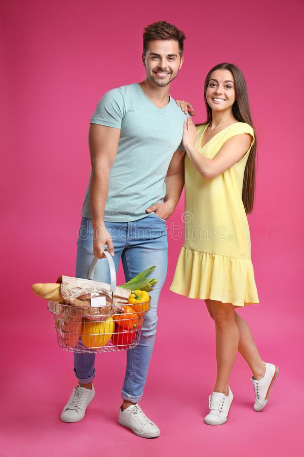 Young couple with shopping basket full of  on pink background stock photos