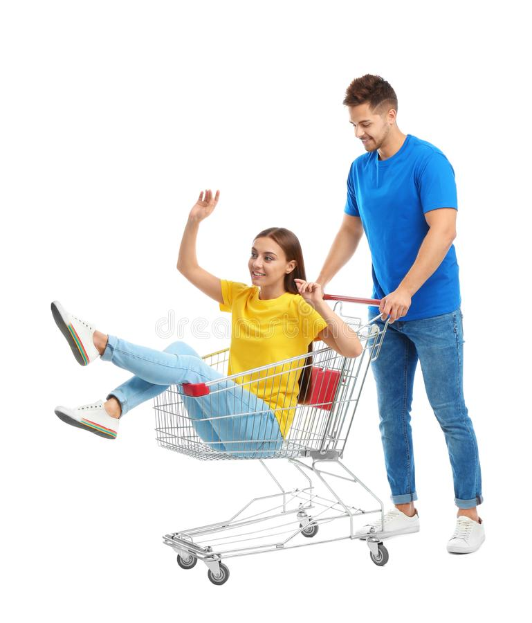 Young couple with shopping cart on background. Young couple with shopping cart on white background stock photos