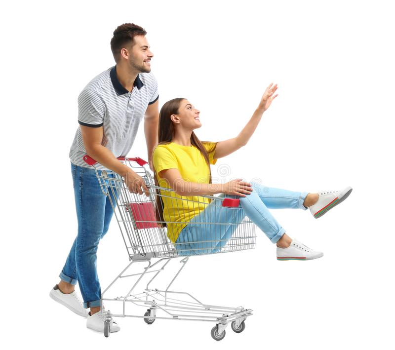 Young couple with shopping cart on background. Young couple with shopping cart on white background royalty free stock photo