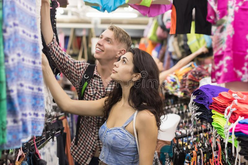 Young Couple On Shopping Choosing Clothes, Man And Woman Buyers Happy Smiling In Retail Store stock image