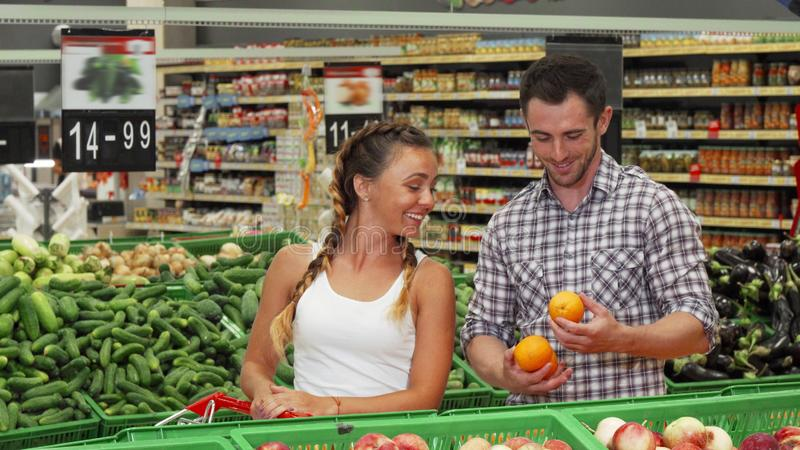 Young couple shopping for groceries at the supermarket. Beautiful young women talking to her handsome boyfriend while shopping for fruits and vegetables at the royalty free stock image