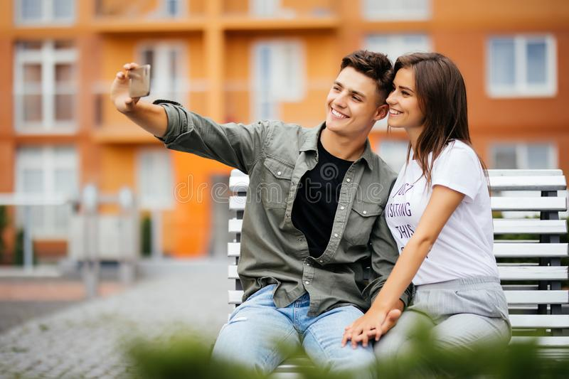 Young couple in shopping. Handsome young couple sitting on the bench and taking a selfie with a mobile phone. Consumerism, fashion, shopping, lifestyle concept stock image