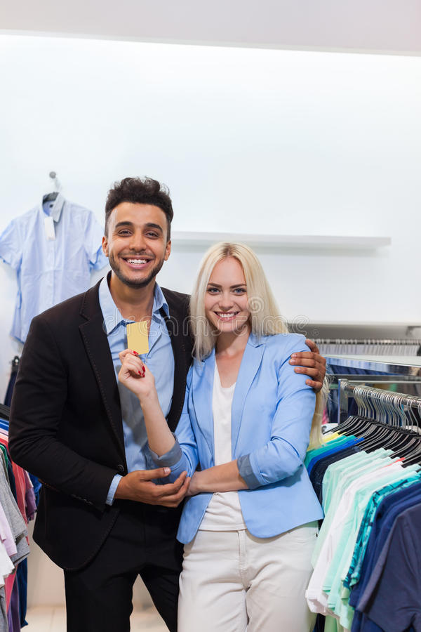 Young Couple Shopping, Happy Smiling Man And Woman Fashion Shop Hold Credit Card royalty free stock images