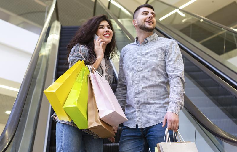 Young couple in shopping mall, going down the escalator royalty free stock image